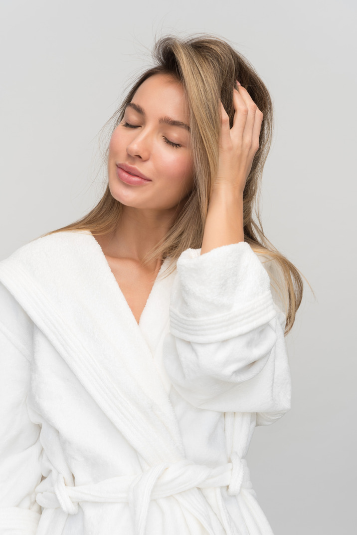 Young beautiful woman with closed eyes touching her hair