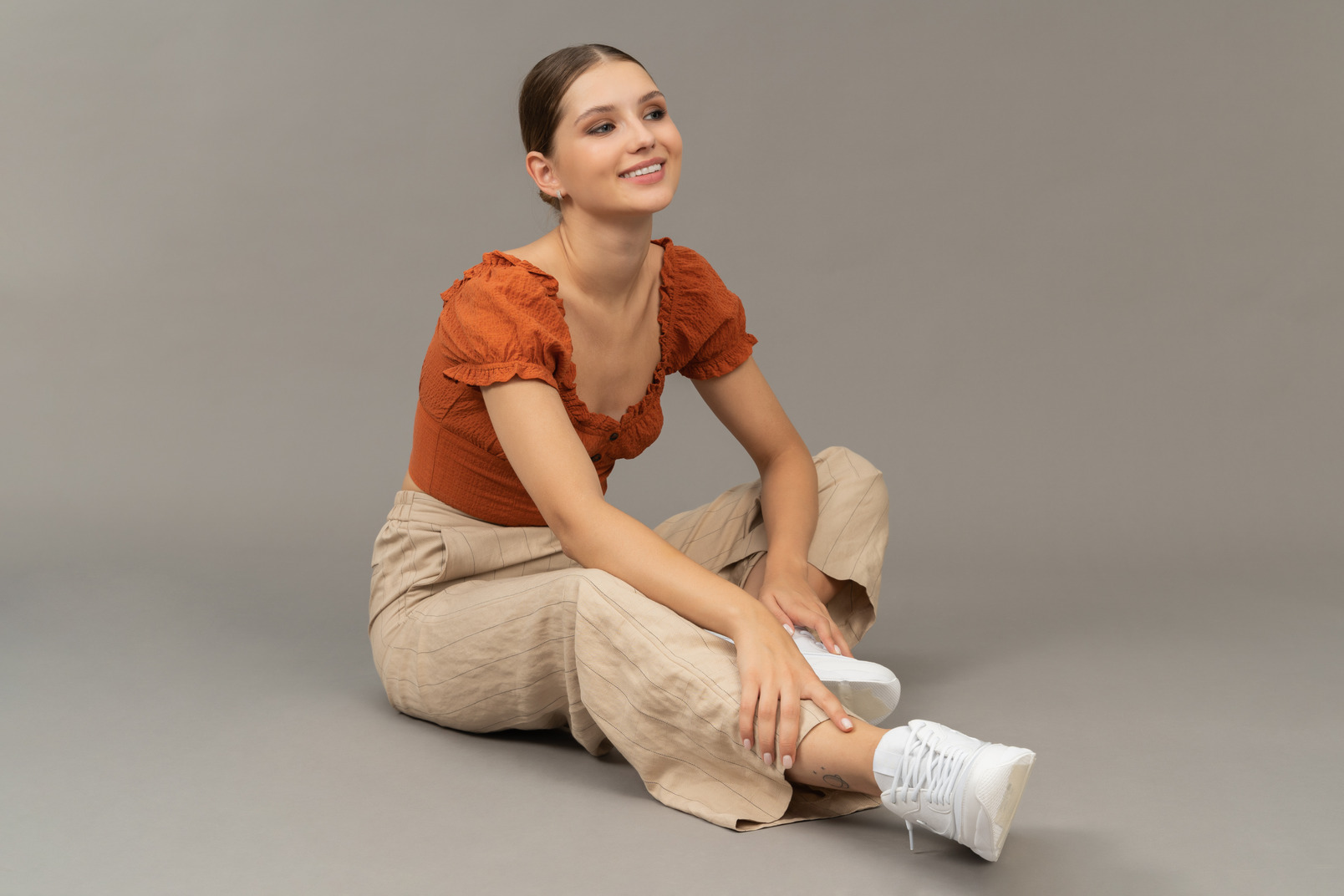 Young woman sits on floor
