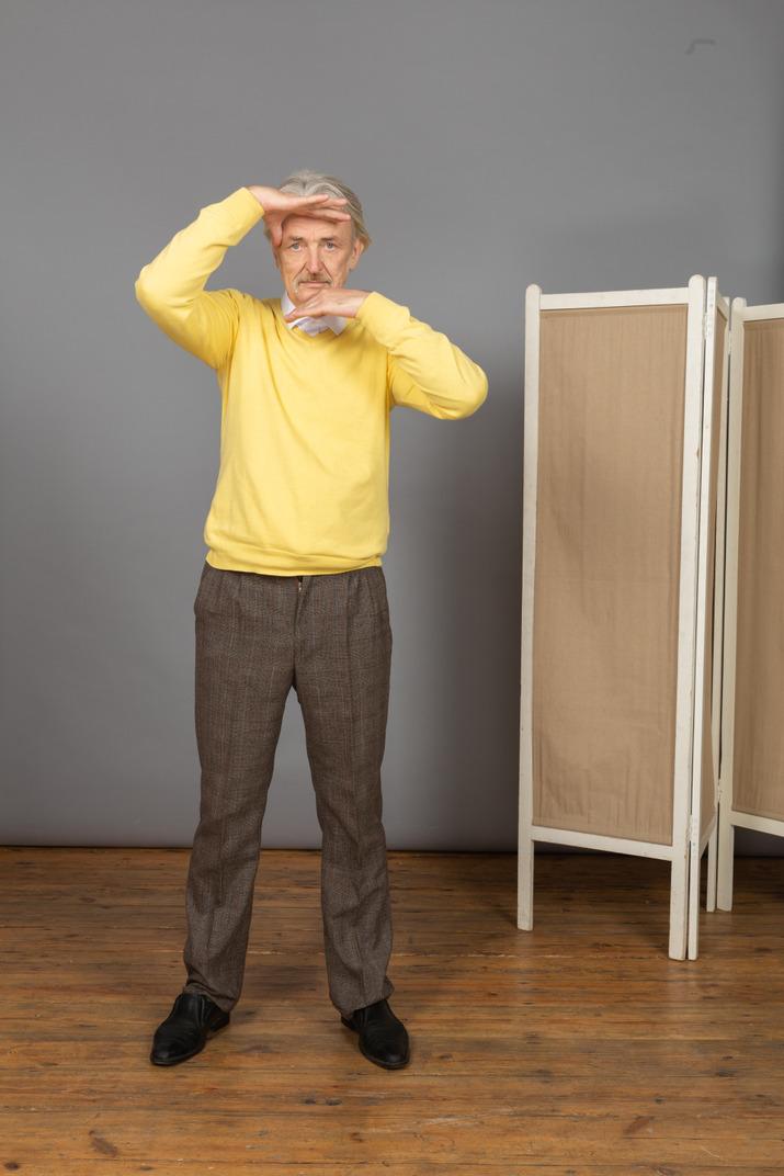 Vista frontal de un anciano levantando las manos mientras mira a la cámara