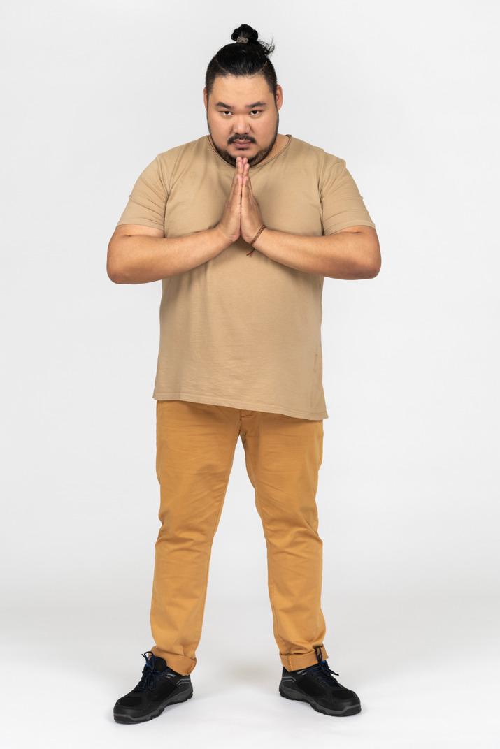 Serious asian man making praying gesture