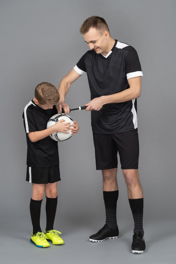 Full-length of a young man coaching little boy