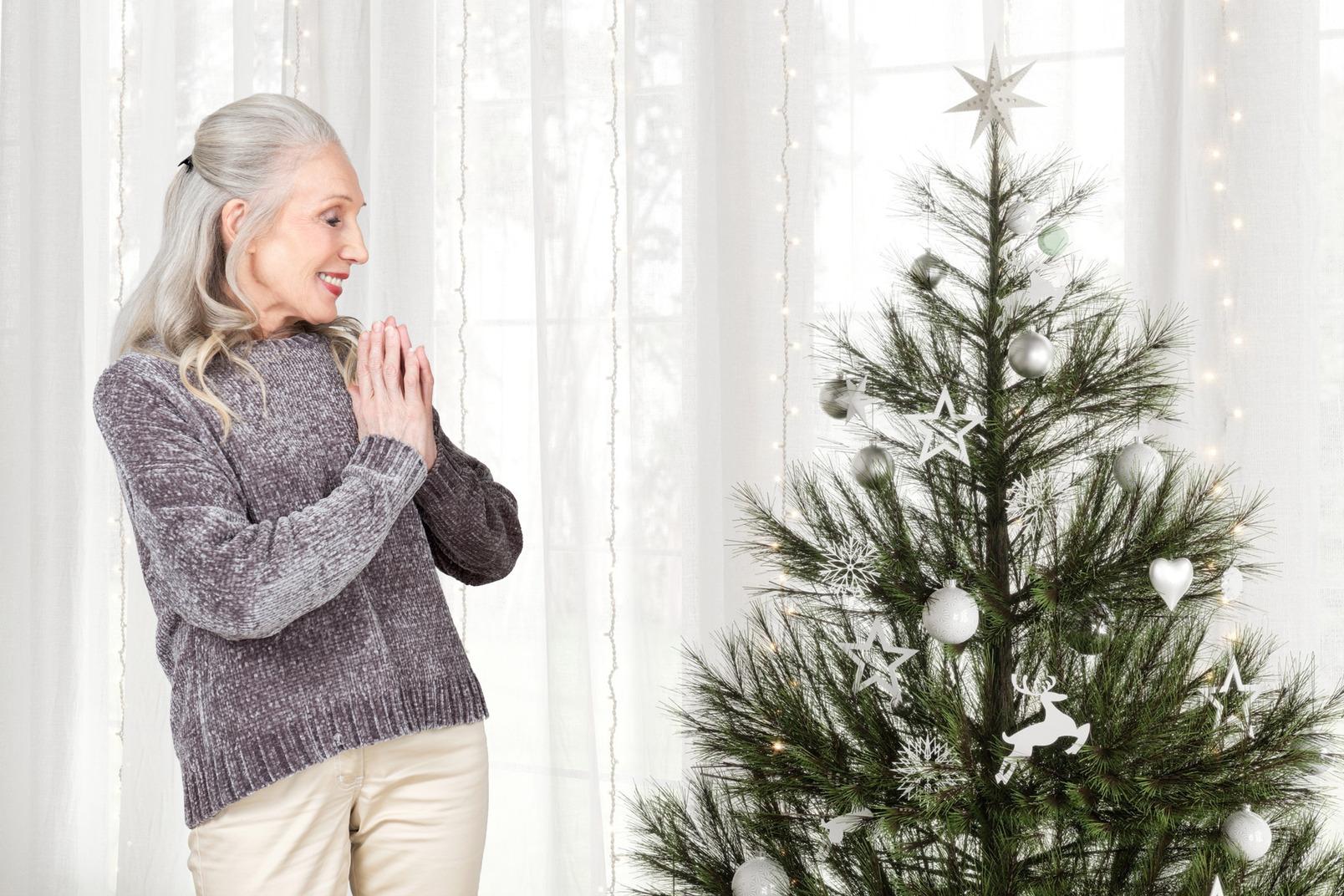 Ältere frau glücklich, geschmückten weihnachtsbaum zu sehen