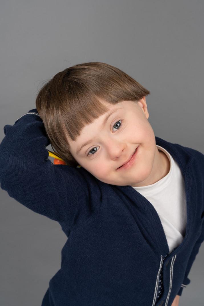 Fröhlicher kleiner junge, der für eine kamera lächelt