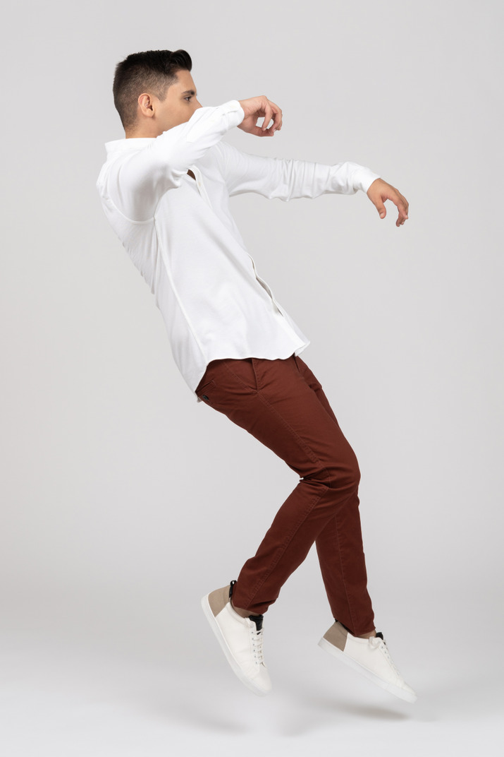Side view of a young latino man jumping and stumbling