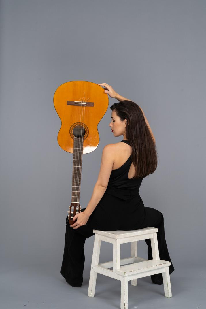 Rückansicht einer jungen dame im schwarzen anzug, die die gitarre kopfüber hält und auf hocker sitzt
