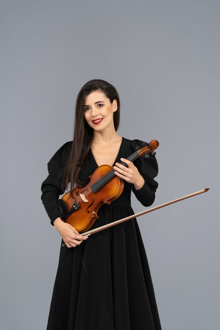 Close-up of a cheerful young lady in black dress holding the violin
