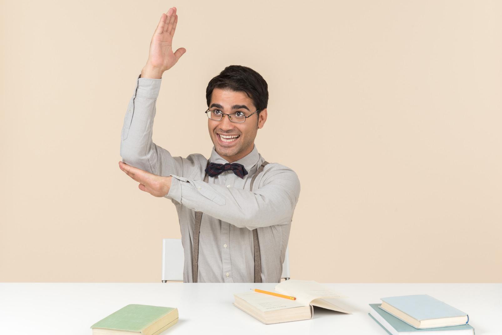 Estudiante adulto sentado en la mesa y levantando una mano