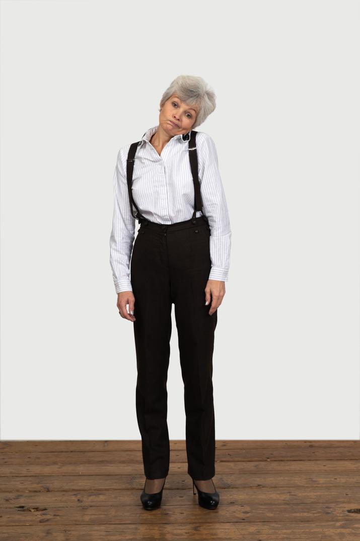 Vorderansicht einer alten unzufriedenen frau in bürokleidung, die sich unwohl fühlt, wenn sie kopf an schulter berührt
