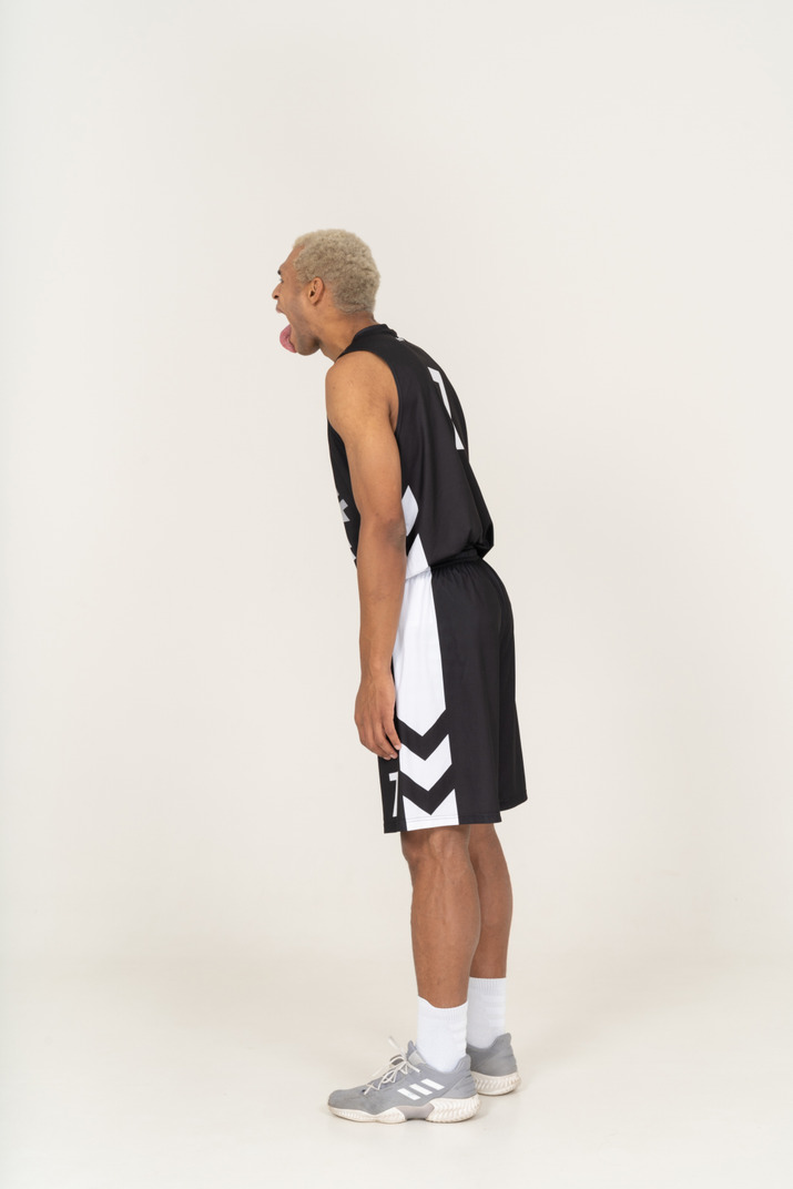 Side view of a crazy young male basketball player showing tongue