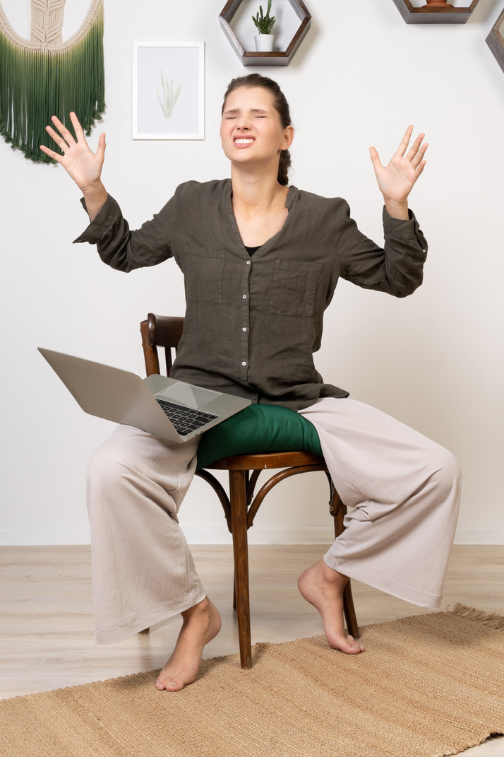 Front view of an irritated young woman with a headache sitting on a chair with a laptop