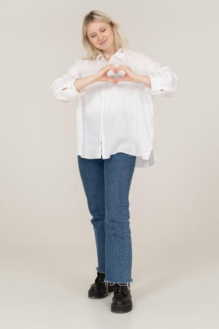 Vorderansicht einer blonden frau in freizeitkleidung, die eine herzgeste mit geschlossenen augen zeigt