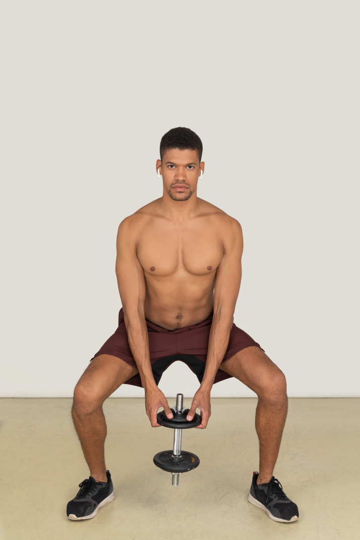 A frontal view of the muscular young guy dressed in red shorts squatting and holding the dumbbell
