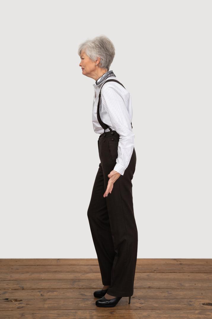 Seitenansicht einer verzogenen alten dame in bürokleidung, die ihre hände ausbreitet