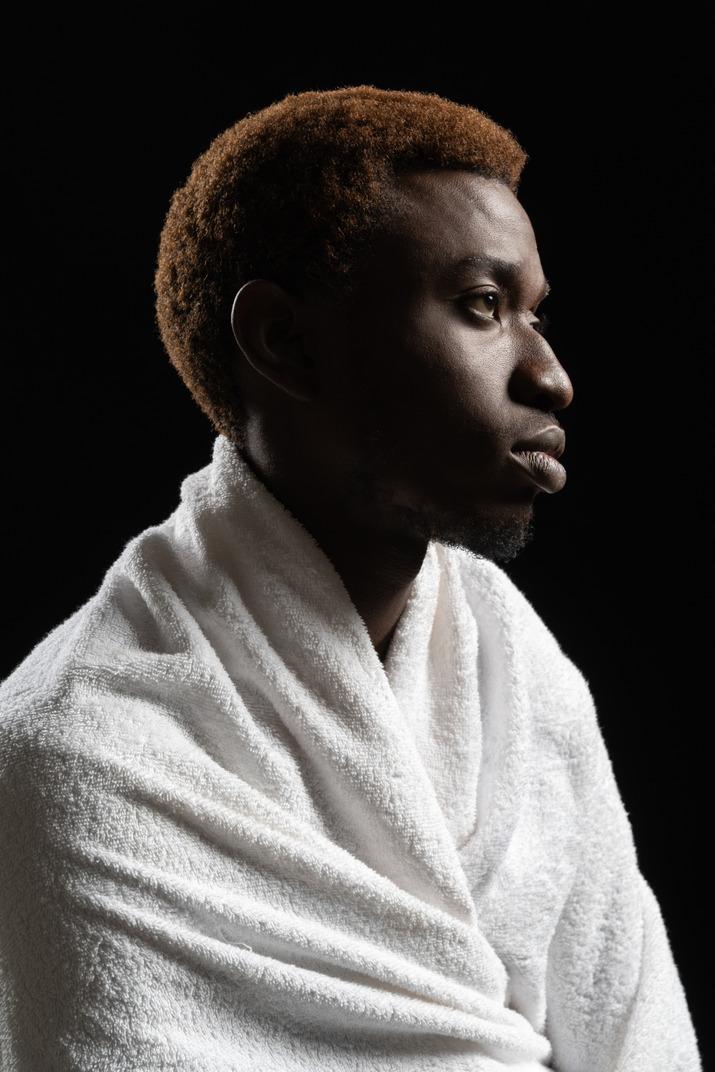 Seitenaufnahme eines jungen mannes, der in ein handtuch gewickelt sitzt
