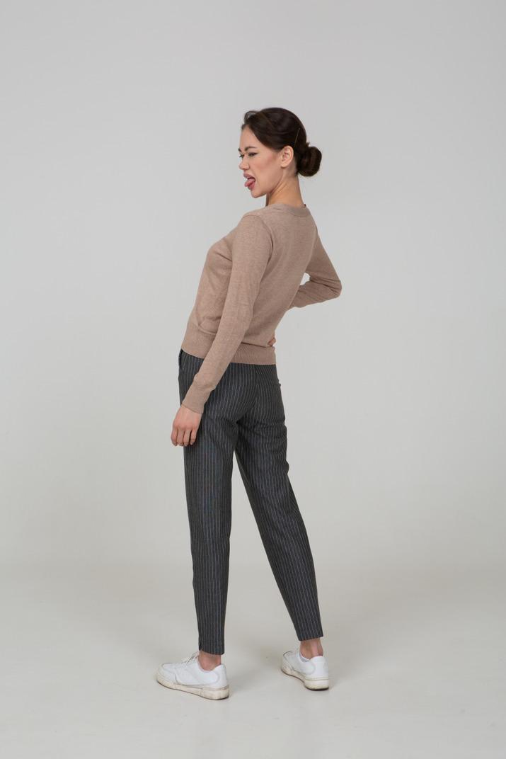 Dreiviertel-rückansicht einer verzogenen jungen dame im beige pullover