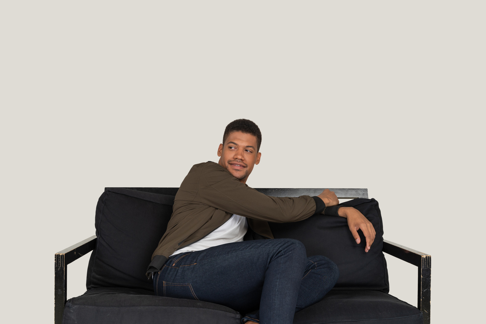 Smiling young man sitting on the sofa