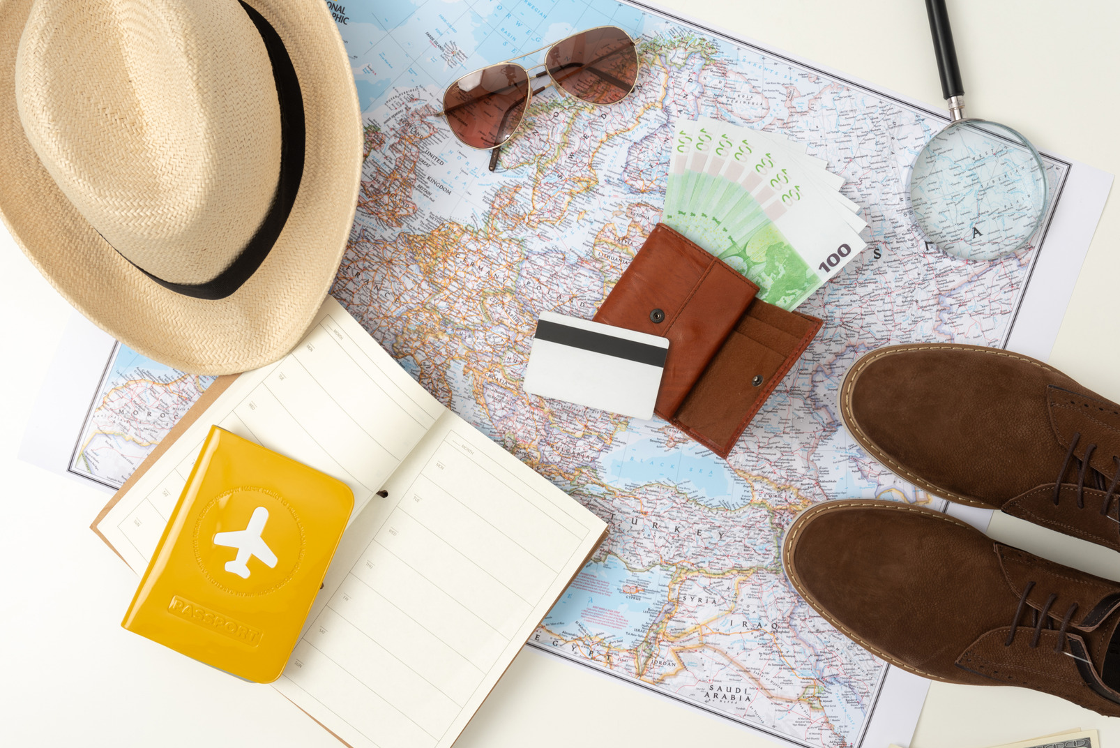 Sunglasses, straw hat, boots, smartphone, international passport and a map with a tourist route lying around the only thing that can replace them all: money