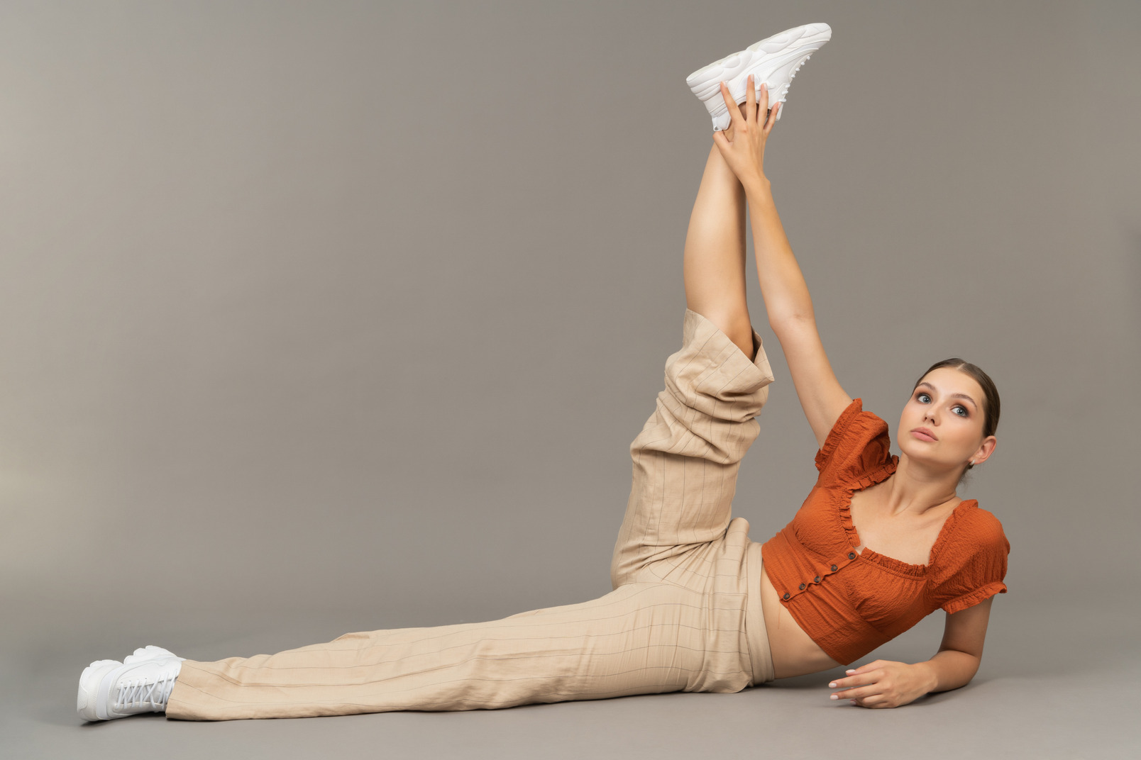 Young woman lies down with stretched leg