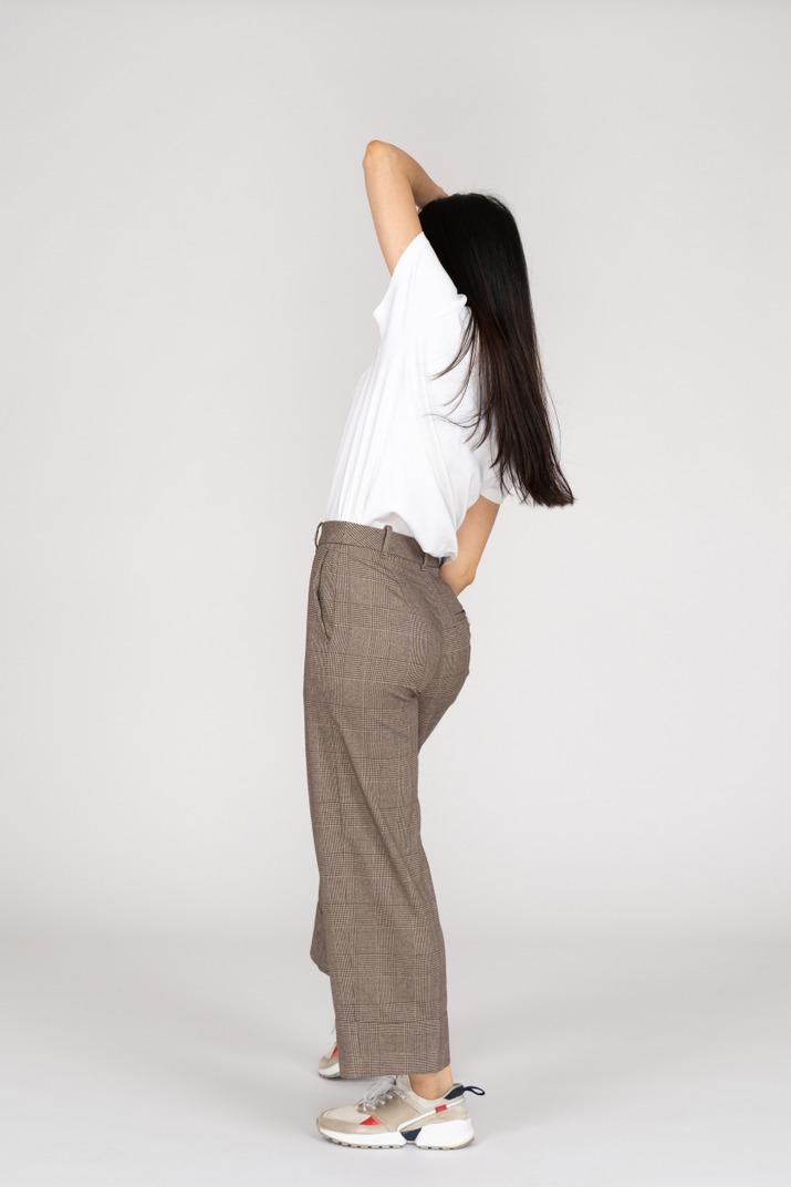 Dreiviertel-rückansicht einer tanzenden jungen dame in reithose und t-shirt, die hände heben