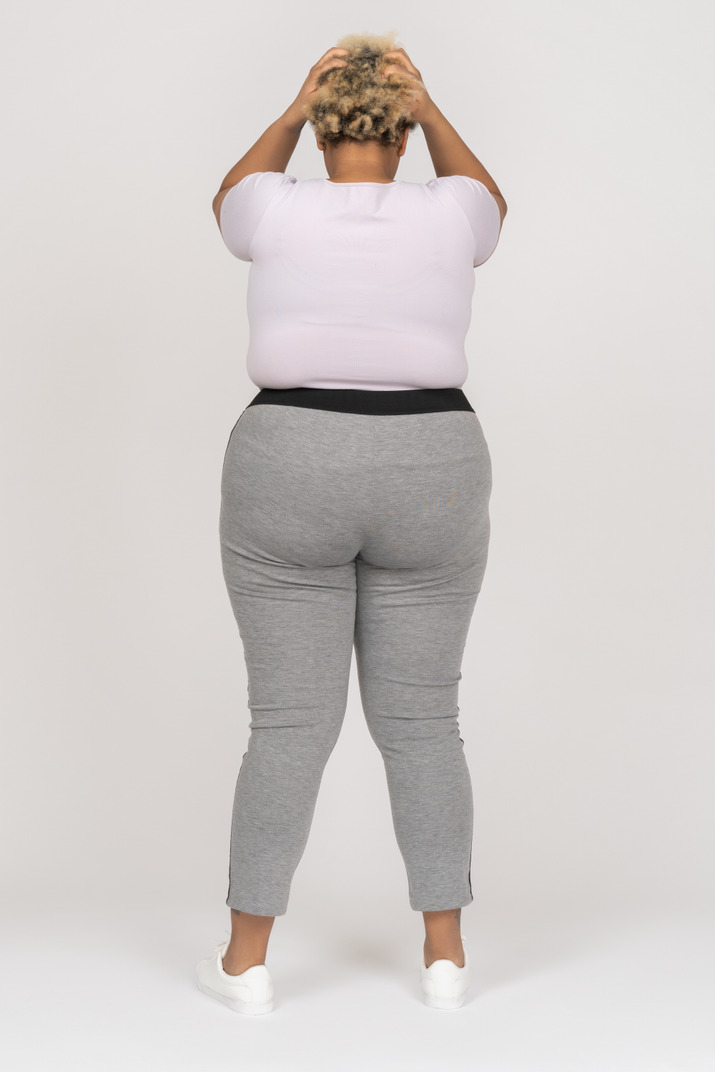 Body positive black woman holding head with both arms back to camera