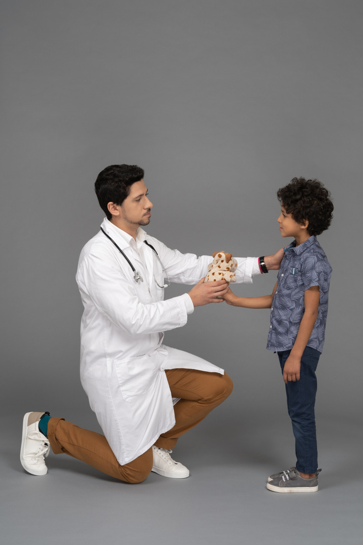 Doctor giving a toy to boy