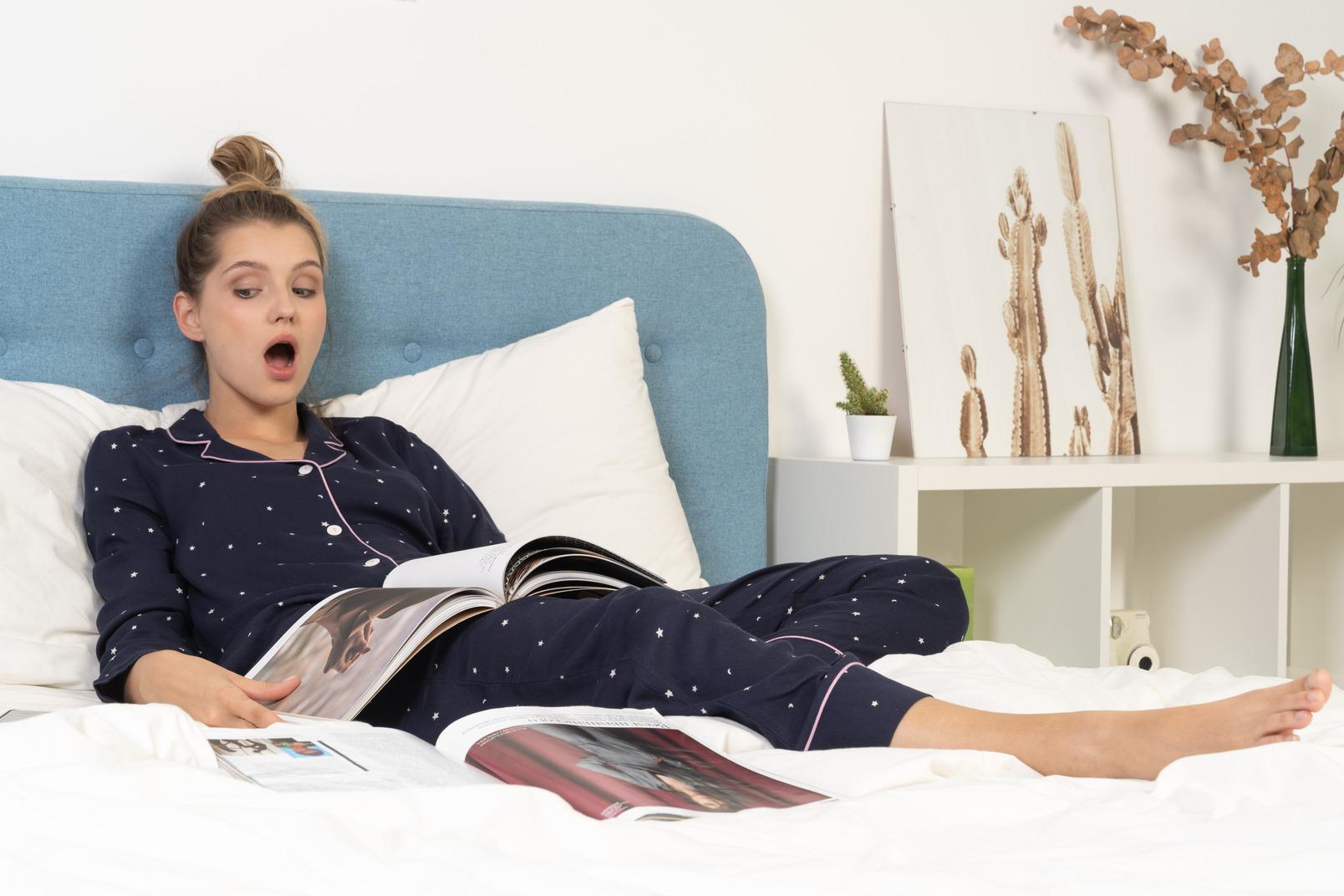 Longitud total de una mujer joven sorprendida en pijama acostado en la cama mientras lee una revista de moda