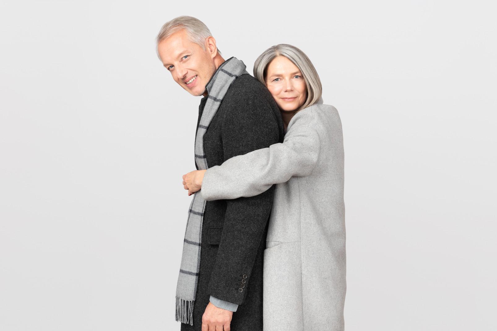 Femme en manteau gris serrant son mari