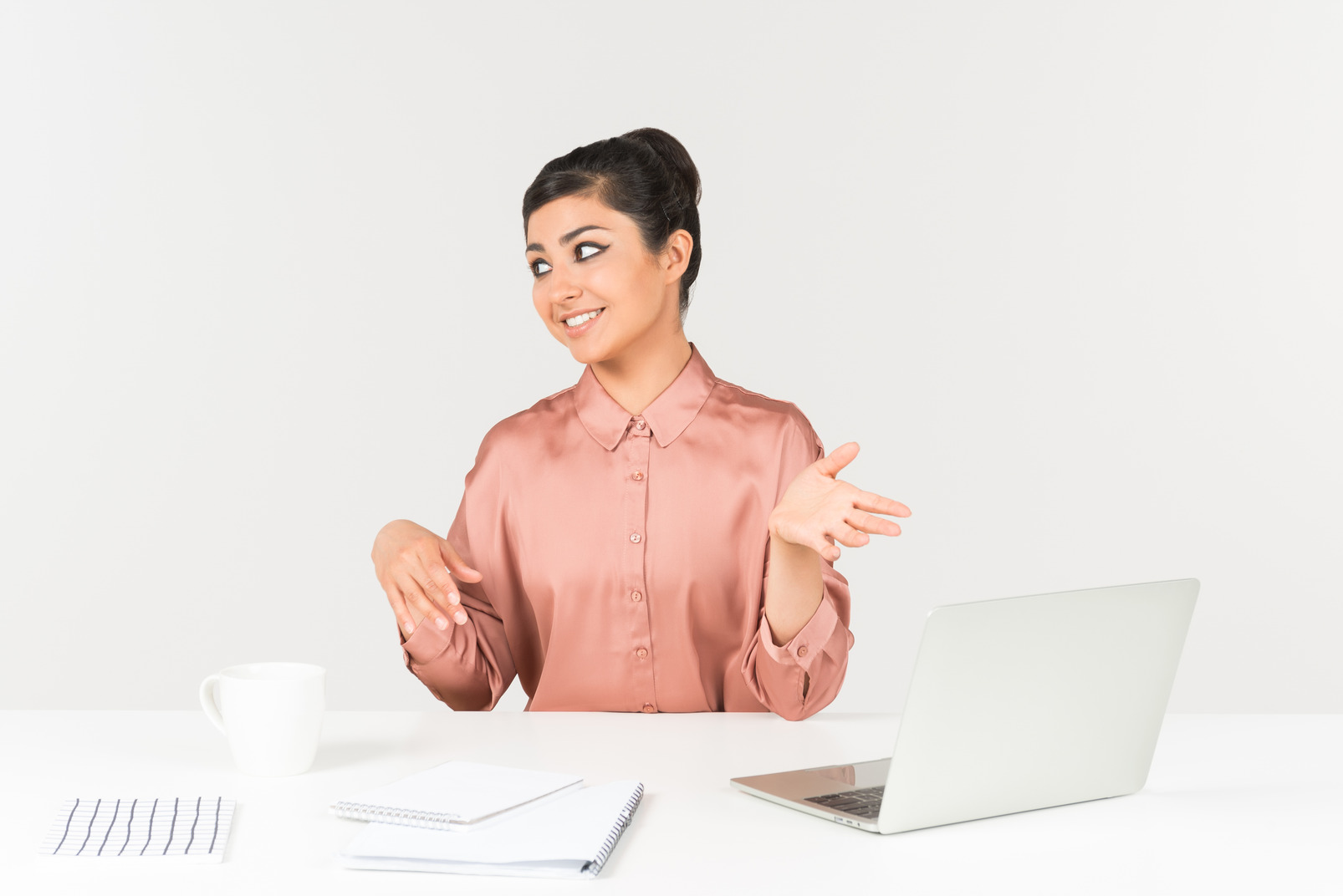 Young indian woman sitting at the office desk and pointing with both hands