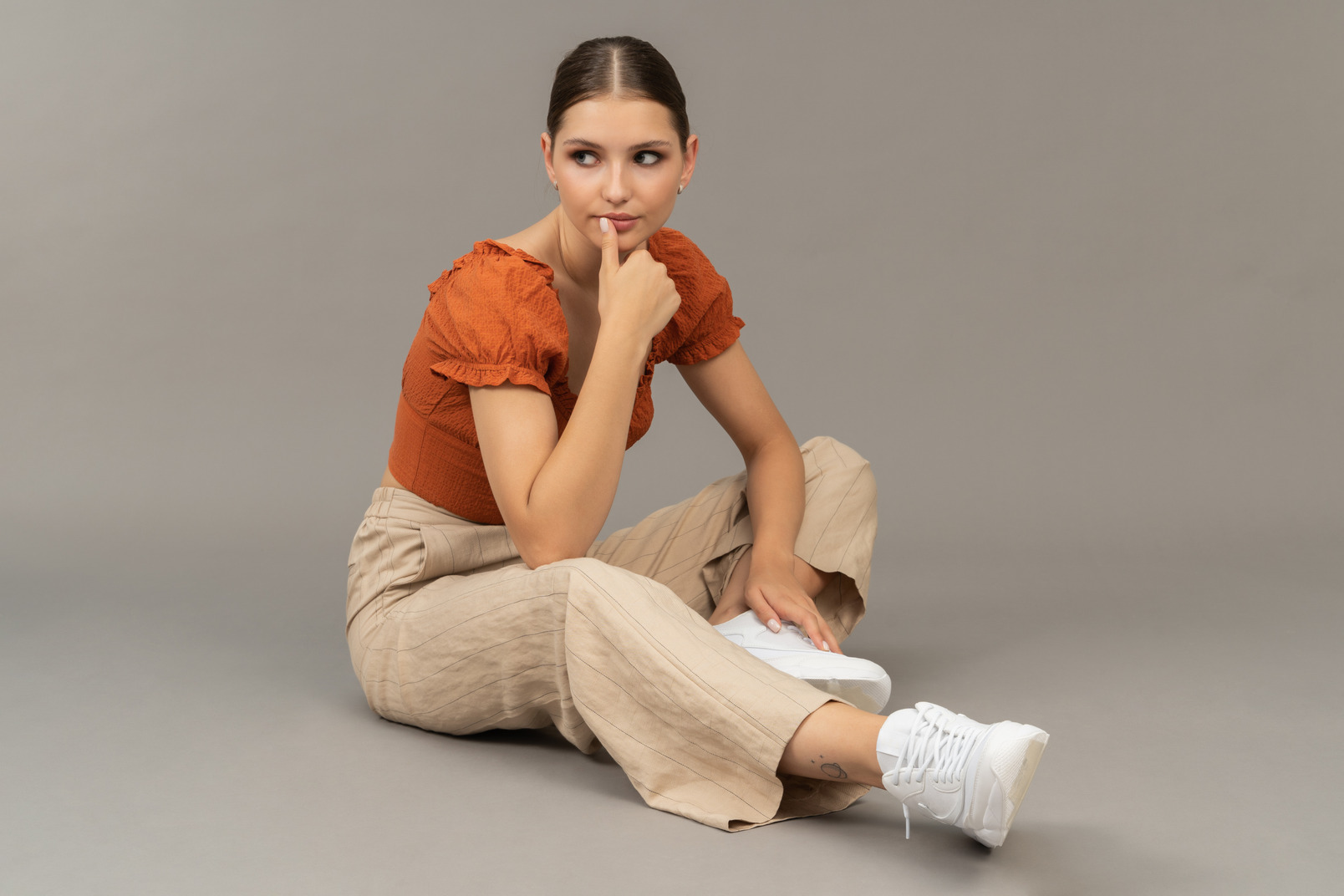 Young woman sits with thumb on her lips
