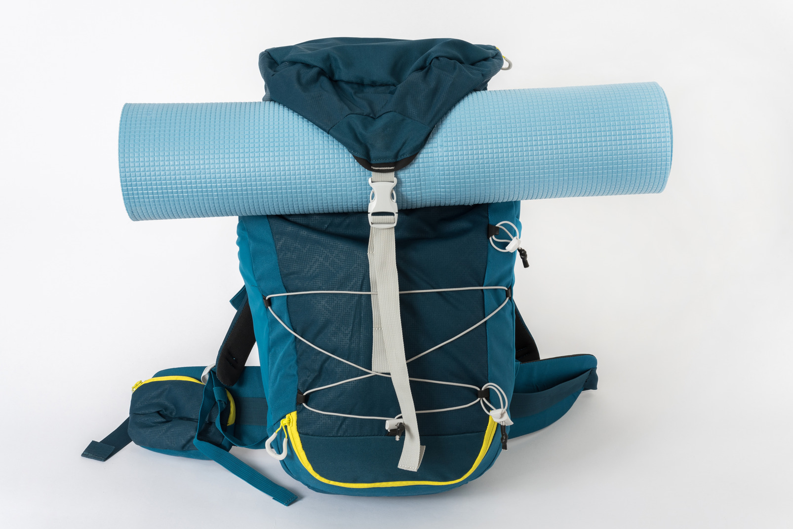 Blue tourist backpack with a yoga mat on a white background