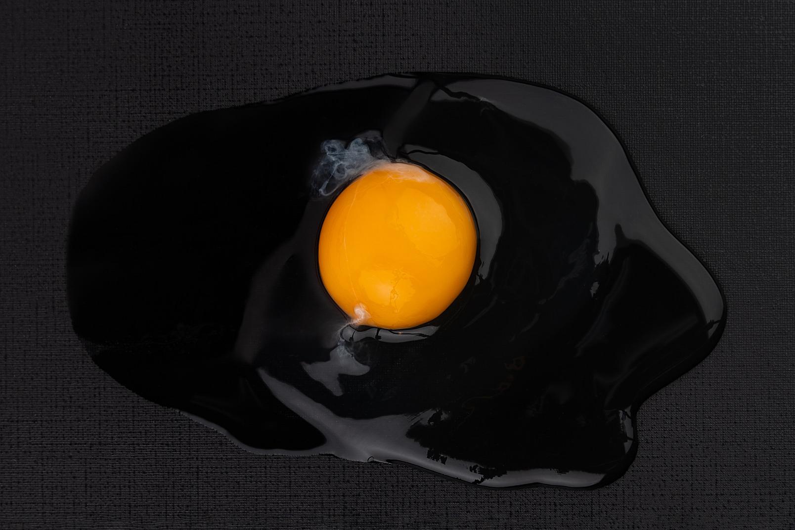 Schalenloses ei auf schwarzem hintergrund