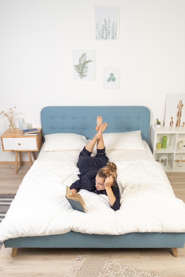ベッドで本を読んで若い女性の正面図