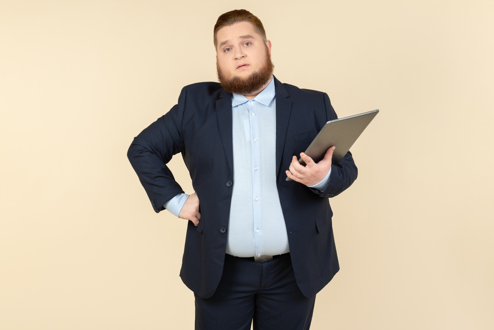 Serious looking young overweight office worker holding digital tablet