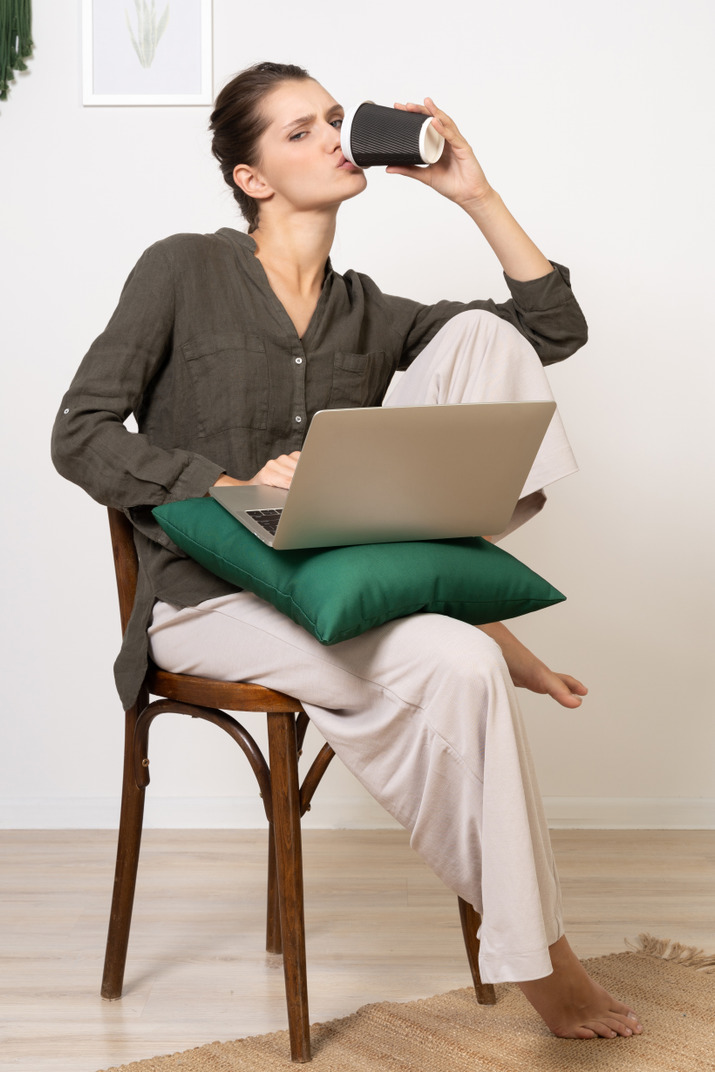 Front view of a young woman sitting on a chair and holding her laptop & drinking coffee