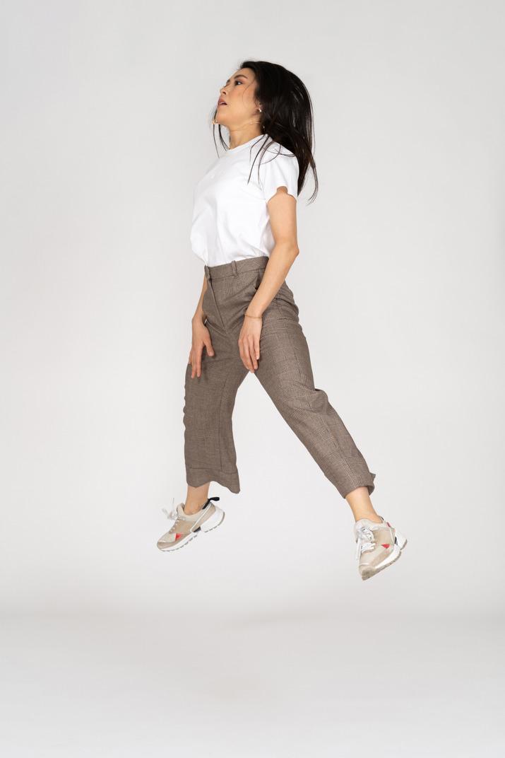 Dreiviertelansicht einer springenden jungen dame in reithose und t-shirt, die ihre beine ausbreitet