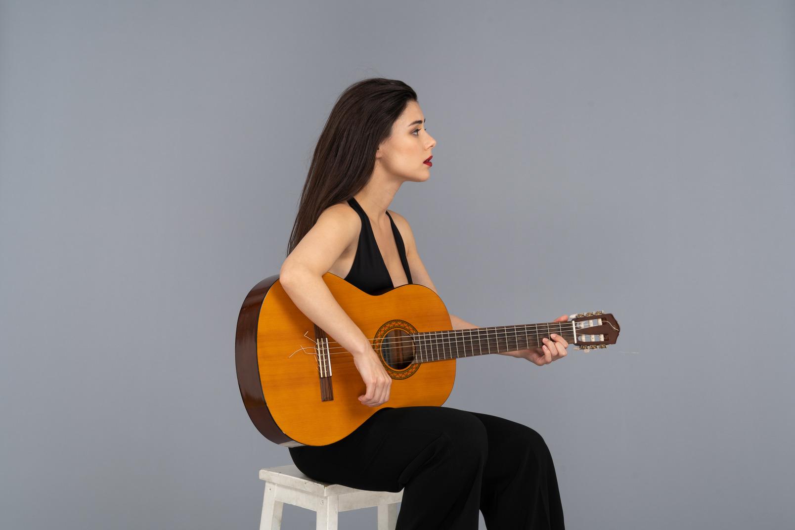Dreiviertelansicht einer sitzenden jungen dame im schwarzen anzug, die gitarre spielt