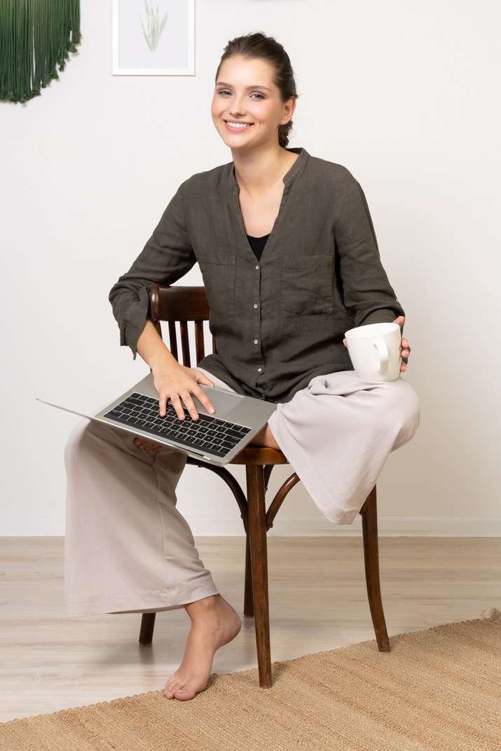 Front view of a young woman wearing home clothes sitting on a chair with a laptop & drinking coffee