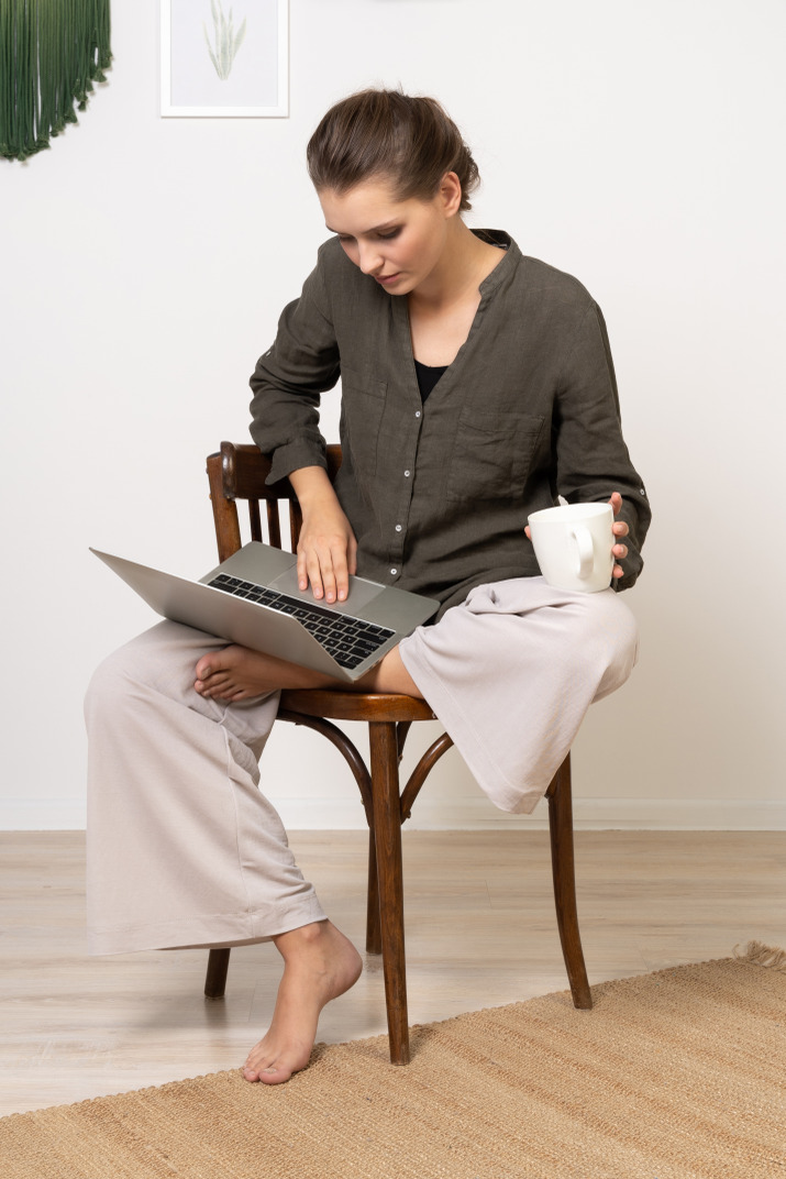 Front view of a young woman sitting on a chair with a laptop & coffee cup