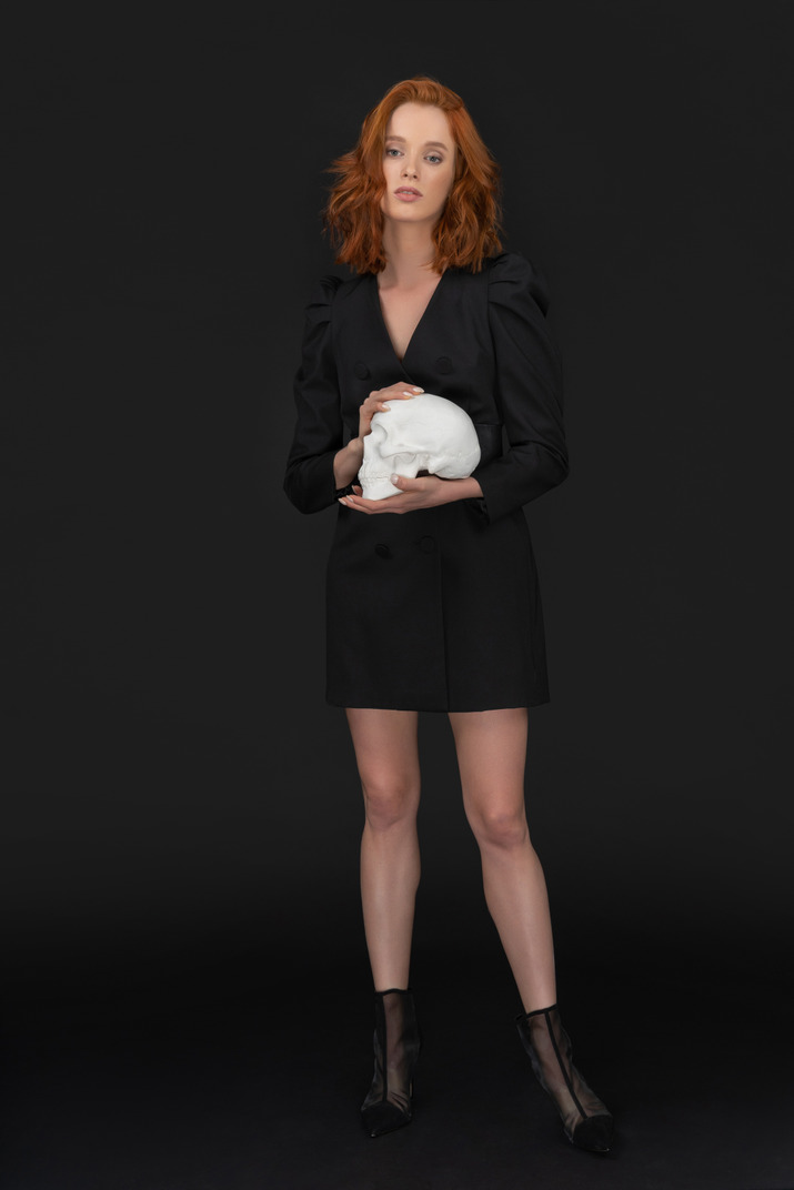 A frontal view of the sexy elegant woman holding a skull and looking to the camera