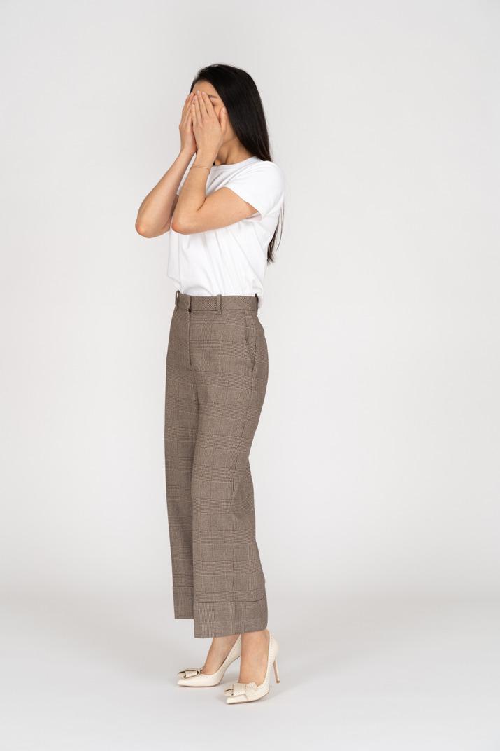 Dreiviertelansicht einer jungen dame in reithose und t-shirt, die ihr gesicht versteckt
