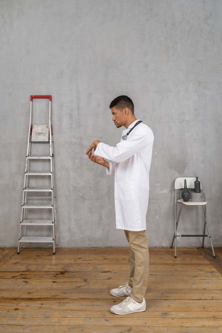 Side view of a young doctor standing in a room with ladder and chair and holding hands together
