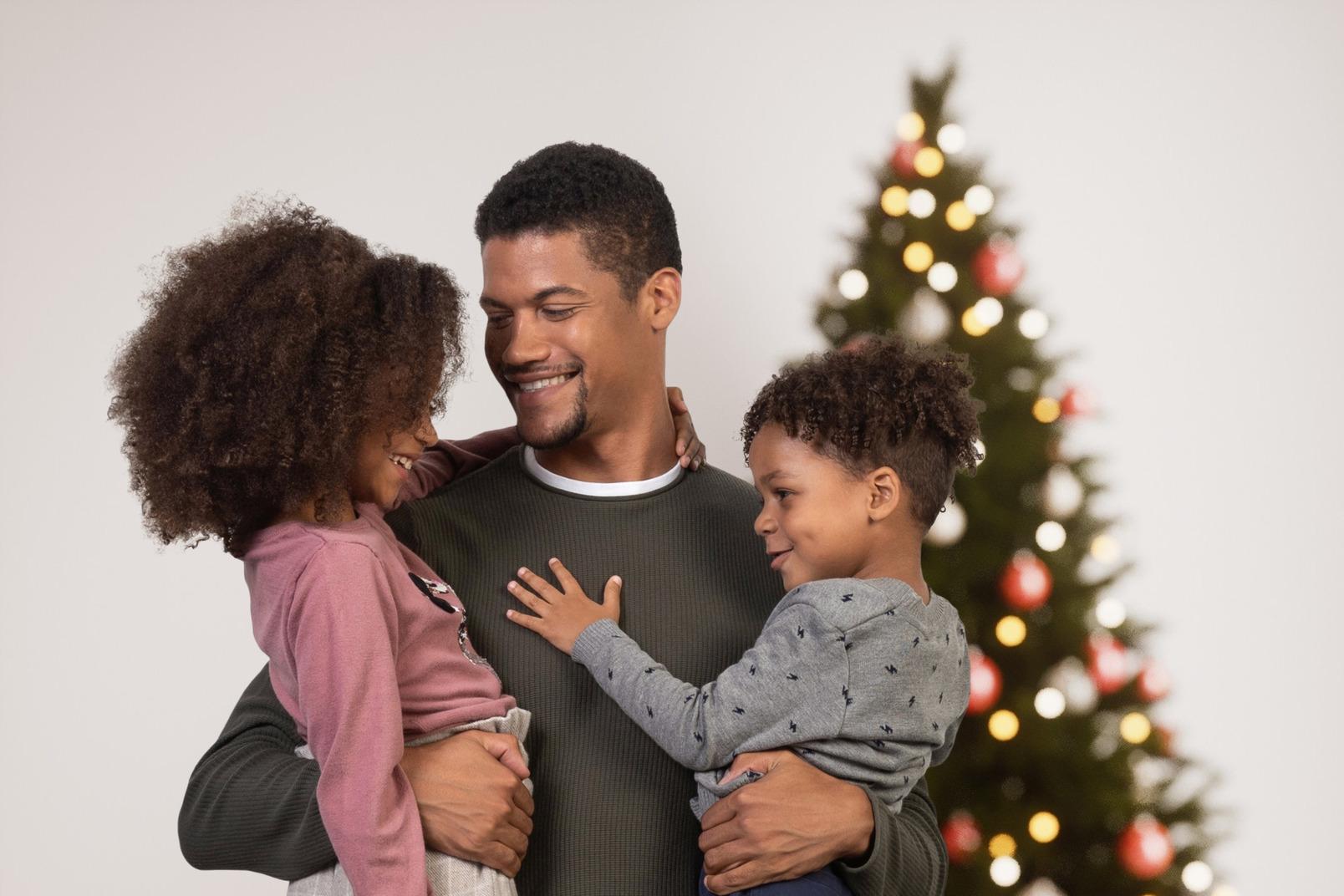 Glücklicher vater mit seinen kindern nahe einem weihnachtsbaum