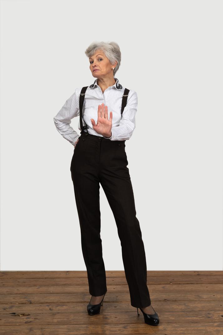 Vorderansicht einer alten unzufriedenen frau in bürokleidung, die eine stoppgeste zeigt