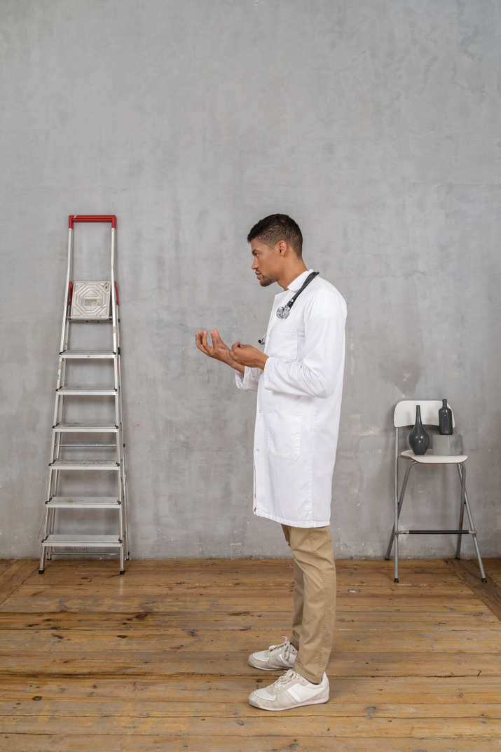 Side view of a young doctor standing in a room with ladder and chair explaining something