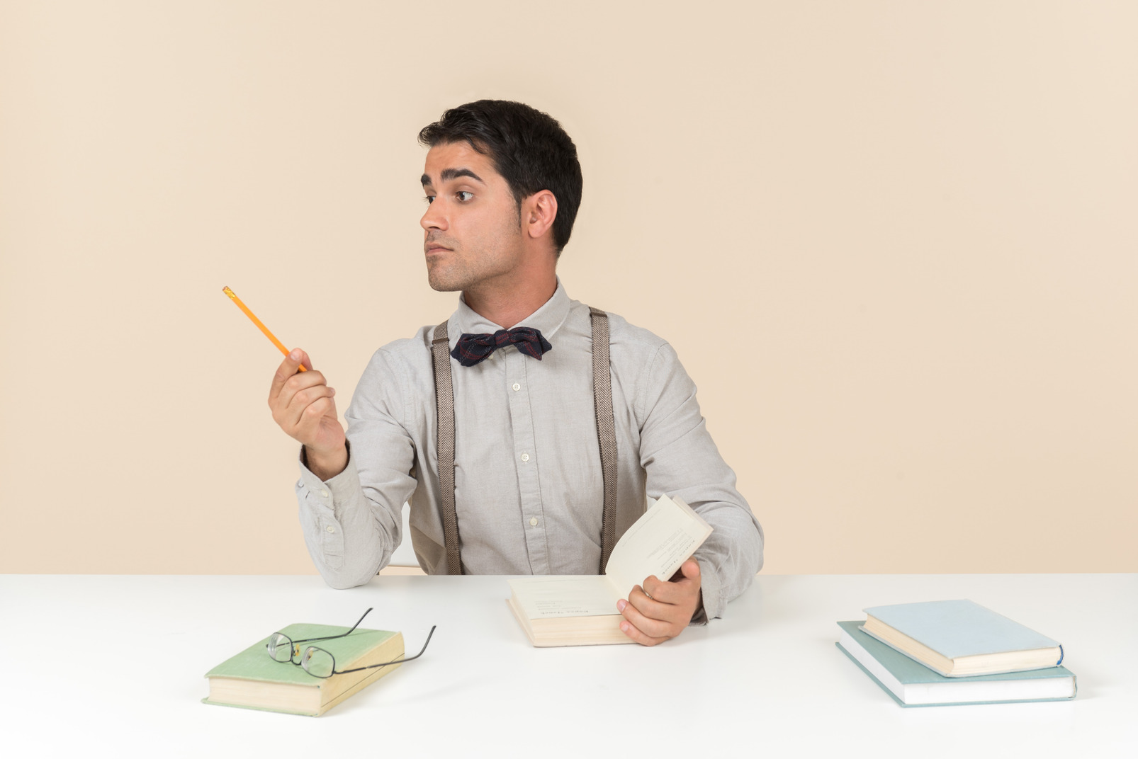 Adult student sitting at the table and pointing aside with a pen
