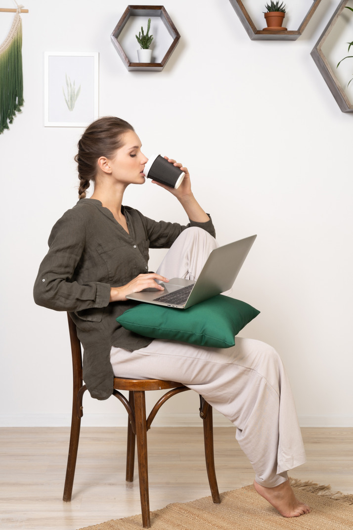 Side view of a perplexed young woman sitting on a chair and holding her laptop & drinking coffee
