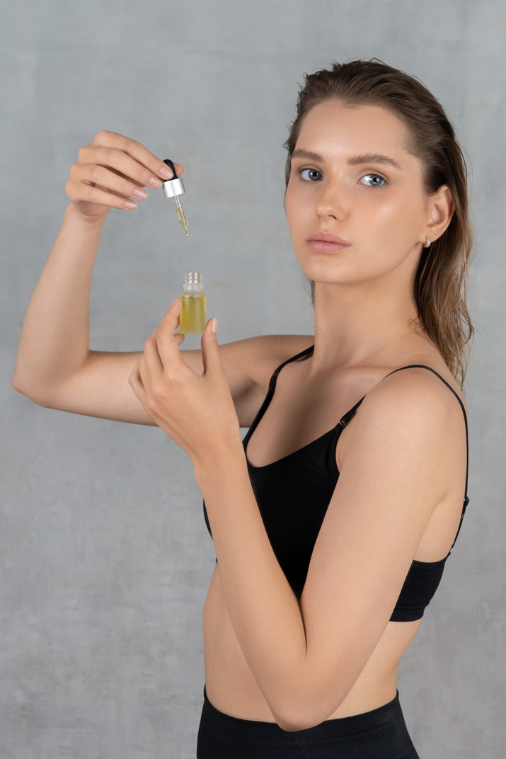 Vista lateral de una mujer joven con suero facial