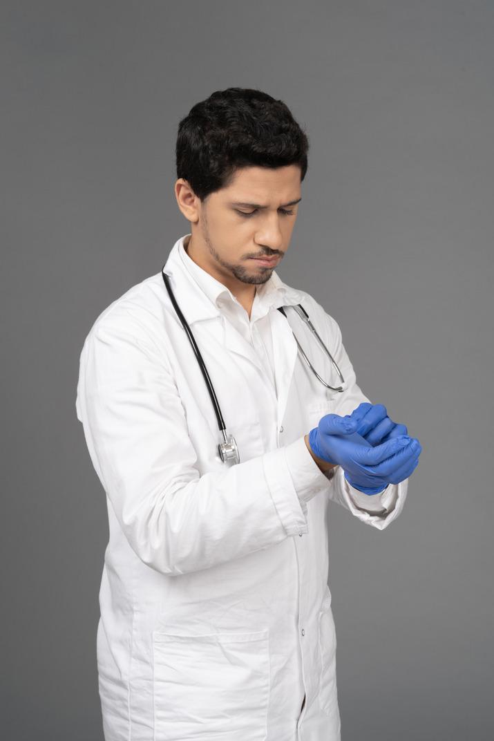 Doctor putting on blue gloves