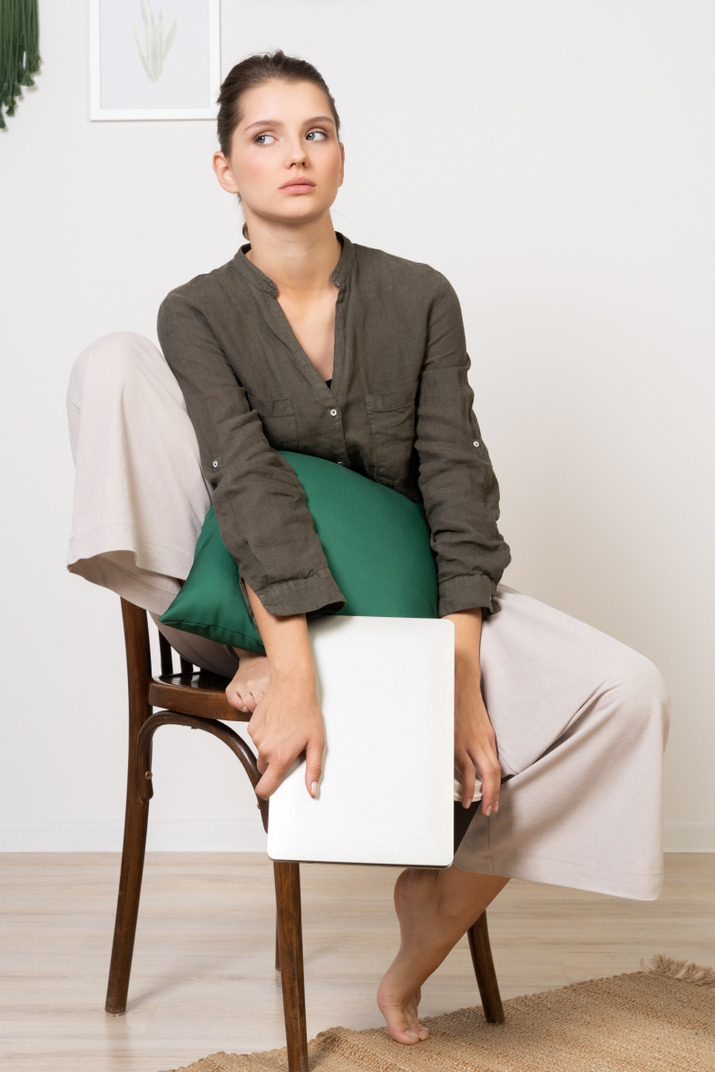 Front view of a confused young woman sitting on a chair and holding her laptop