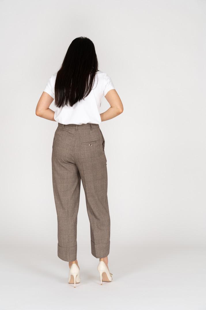 Rückansicht einer jungen dame in reithose und t-shirt, die ihren bauch berührt